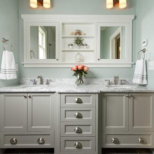 Modelo de cuarto de baño principal, tradicional, de tamaño medio, con lavabo bajoencimera, armarios estilo shaker, puertas de armario grises, encimera de mármol, paredes azules y suelo de baldosas de cerámica