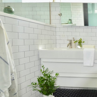 Example of a mid-sized minimalist master white tile and subway tile ceramic floor and black floor bathroom design in New York with flat-panel cabinets, white cabinets, a one-piece toilet, black walls, an integrated sink, solid surface countertops and white countertops