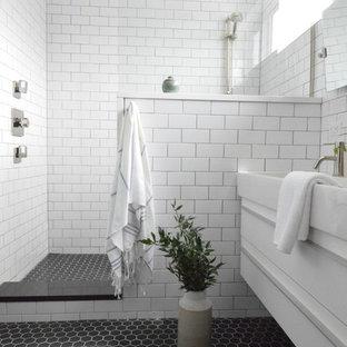 Идея дизайна: главная ванная комната среднего размера в стиле модернизм с плоскими фасадами, белыми фасадами, открытым душем, унитазом-моноблоком, белой плиткой, плиткой кабанчик, черными стенами, полом из керамической плитки, монолитной раковиной, столешницей из искусственного камня, черным полом, открытым душем и белой столешницей