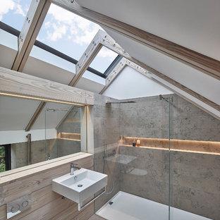Immagine di una stanza da bagno contemporanea con lavabo sospeso, doccia a filo pavimento, WC sospeso, piastrelle grigie, piastrelle in pietra e pavimento in legno massello medio