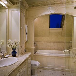 Cette photo montre une salle de bain principale chic de taille moyenne avec un placard à porte affleurante, des portes de placard beiges, une baignoire posée, une douche d'angle, un urinoir, un carrelage beige, un mur noir, un sol en calcaire, un lavabo posé, un plan de toilette en calcaire, un sol beige et une cabine de douche à porte battante.