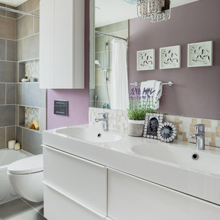Bathroom - small contemporary kids' glass tile ceramic floor and gray floor bathroom idea in Denver with flat-panel cabinets, white cabinets, a wall-mount toilet, purple walls, an integrated sink, solid surface countertops and white countertops