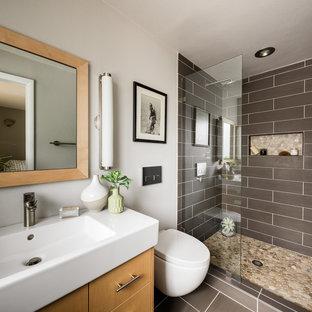 デンバーの小さいコンテンポラリースタイルのおしゃれな子供用バスルーム (フラットパネル扉のキャビネット、白いキャビネット、アルコーブ型浴槽、シャワー付き浴槽、壁掛け式トイレ、ガラスタイル、紫の壁、セラミックタイルの床、一体型シンク、人工大理石カウンター、グレーの床、シャワーカーテン、白い洗面カウンター) の写真