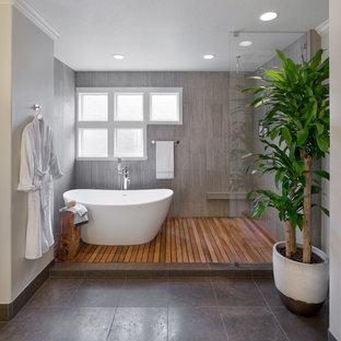 Inspiration pour une grand salle de bain principale asiatique avec une baignoire indépendante, une douche ouverte, un carrelage marron, des carreaux de céramique et un mur gris.
