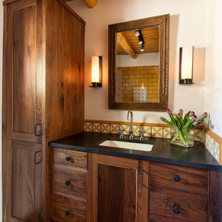 This is an example of a small mediterranean shower room bathroom in Albuquerque with shaker cabinets, dark wood cabinets, a walk-in shower, yellow tiles, metro tiles, terracotta flooring, a submerged sink and engineered stone worktops.