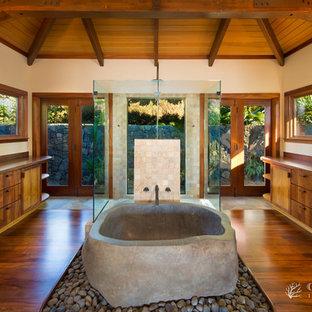 Foto de cuarto de baño principal, exótico, grande, con puertas de armario de madera oscura, encimera de madera, bañera exenta, ducha abierta, paredes beige y suelo de madera clara