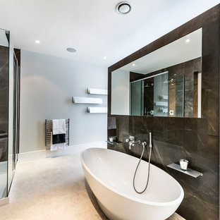 This is an example of a large traditional ensuite bathroom in Other with a freestanding bath, a corner shower, black tiles, marble tiles, grey walls, beige floors and a sliding door.
