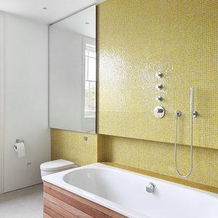 Immagine di una stanza da bagno per bambini minimalista di medie dimensioni con vasca ad angolo, vasca/doccia, WC monopezzo, piastrelle gialle, piastrelle in ceramica, pareti bianche, pavimento in gres porcellanato e pavimento bianco