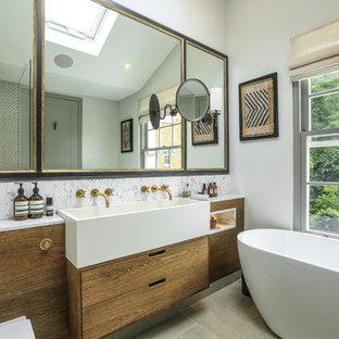 Diseño de cuarto de baño contemporáneo con armarios con paneles lisos, puertas de armario de madera oscura, bañera exenta, paredes blancas, lavabo de seno grande, suelo gris y encimeras blancas