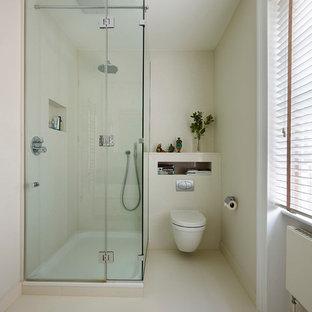 Foto de cuarto de baño principal, clásico, pequeño, con armarios tipo mueble, puertas de armario blancas, ducha esquinera, sanitario de pared, baldosas y/o azulejos blancos, baldosas y/o azulejos de porcelana, paredes blancas y suelo de baldosas de porcelana