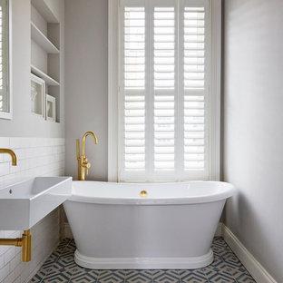 Esempio di una stanza da bagno nordica con nessun'anta, vasca freestanding, piastrelle bianche, piastrelle diamantate, pareti grigie, pavimento in cementine, lavabo integrato e pavimento blu