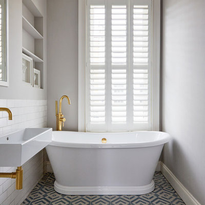 Danish white tile and subway tile cement tile floor and blue floor freestanding bathtub photo in London with open cabinets, gray walls and an integrated sink