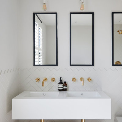 Danish white tile and ceramic tile bathroom photo in London with open cabinets, white walls, an integrated sink and white countertops