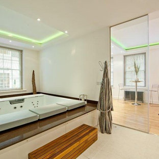 Photo of a medium sized contemporary bathroom in London with a japanese bath, white walls and grey floors.