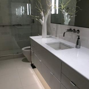На фото: со средним бюджетом маленькие главные ванные комнаты в стиле модернизм с стеклянными фасадами, серыми фасадами, открытым душем, унитазом-моноблоком, белой плиткой, керамической плиткой, серыми стенами, полом из керамогранита, врезной раковиной, столешницей из искусственного кварца, белым полом, открытым душем и белой столешницей