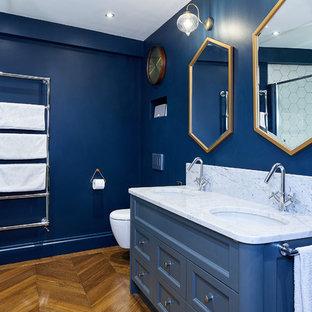 Foto de cuarto de baño infantil, actual, pequeño, con armarios tipo mueble, puertas de armario azules, bañera encastrada, ducha abierta, sanitario de pared, baldosas y/o azulejos blancos, baldosas y/o azulejos en mosaico, paredes azules, suelo de madera clara, lavabo encastrado, encimera de mármol, suelo marrón y ducha abierta