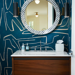 Inspiration for a large midcentury 3/4 bathroom in Grand Rapids with flat-panel cabinets, brown cabinets, a two-piece toilet, blue walls, light hardwood floors, an integrated sink, engineered quartz benchtops, brown floor and white benchtops.