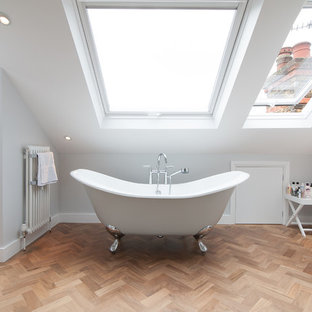 Example of a trendy master light wood floor claw-foot bathtub design in Other