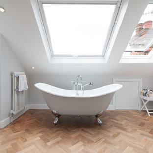 Immagine di una stanza da bagno padronale design con vasca con piedi a zampa di leone e parquet chiaro