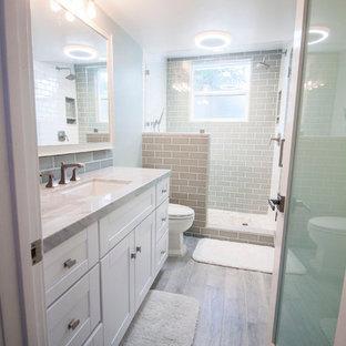 Удачное сочетание для дизайна помещения: маленькая ванная комната в современном стиле с фасадами в стиле шейкер, белыми фасадами, душем в нише, унитазом-моноблоком, синей плиткой, стеклянной плиткой, синими стенами, полом из керамогранита, душевой кабиной, врезной раковиной и мраморной столешницей - самое интересное для вас