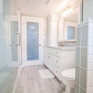Immagine di una piccola stanza da bagno con doccia design con ante in stile shaker, ante bianche, doccia alcova, WC monopezzo, piastrelle blu, piastrelle di vetro, pareti blu, pavimento in gres porcellanato, lavabo sottopiano e top in marmo