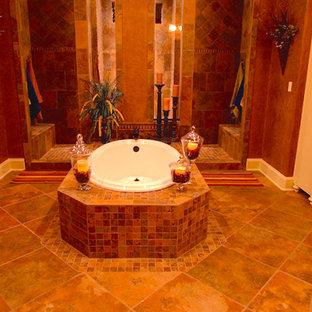 Immagine di una piccola sauna tropicale con lavabo a bacinella, ante con riquadro incassato, ante beige, top piastrellato, vasca freestanding, piastrelle nere, piastrelle in ceramica, pareti gialle e pavimento con piastrelle a mosaico