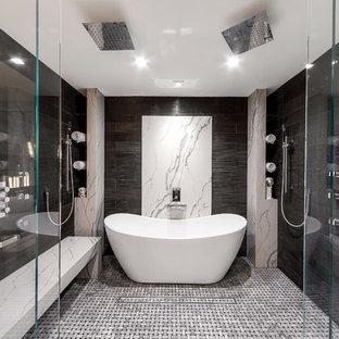 Diseño de cuarto de baño principal, actual, grande, con armarios con paneles lisos, puertas de armario de madera oscura, bañera exenta, ducha a ras de suelo, paredes grises, baldosas y/o azulejos grises, suelo con mosaicos de baldosas, suelo gris, ducha abierta y encimeras blancas