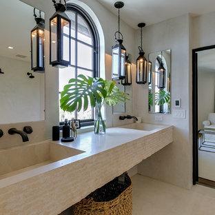 На фото: ванная комната в средиземноморском стиле с бежевой плиткой, полом из известняка, подвесной раковиной, столешницей из гранита и бежевым полом с