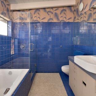 Ejemplo de cuarto de baño principal, bohemio, con armarios con paneles lisos, bañera encastrada, ducha abierta, baldosas y/o azulejos azules, baldosas y/o azulejos de cerámica, suelo de baldosas tipo guijarro, lavabo sobreencimera y ducha con puerta con bisagras