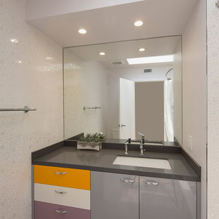 Photo of a contemporary kids bathroom in Los Angeles with an undermount sink, flat-panel cabinets, grey cabinets, a shower/bathtub combo, white tile, mosaic tile, white walls, limestone benchtops and light hardwood floors.