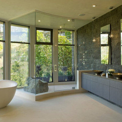 Trendy freestanding bathtub photo in Los Angeles with a vessel sink