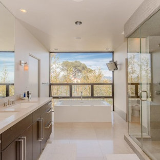 Example of a large trendy master beige tile and glass sheet limestone floor and beige floor bathroom design in Los Angeles with flat-panel cabinets, dark wood cabinets, a one-piece toilet, white walls, an undermount sink, limestone countertops, a hinged shower door and beige countertops
