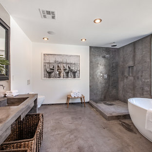 Example of a large trendy master gray tile and cement tile gray floor and concrete floor bathroom design in Los Angeles with white walls, a trough sink, gray countertops, open cabinets, a wall-mount toilet and concrete countertops