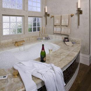 Exemple d'une salle de bain principale tendance de taille moyenne avec un lavabo encastré, un placard à porte plane, une baignoire encastrée, une douche d'angle, un carrelage en pâte de verre, un mur beige, un sol en bois foncé, un carrelage beige, des portes de placard violettes, un WC à poser, un plan de toilette en onyx, un sol marron, une cabine de douche à porte battante et un plan de toilette beige.