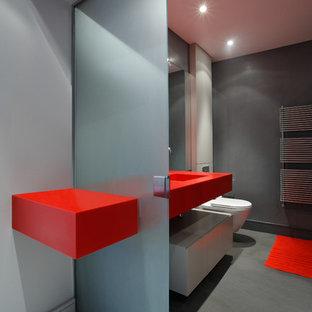 Imagen de cuarto de baño ecléctico, de tamaño medio, con armarios con paneles lisos, puertas de armario rojas, paredes grises y suelo gris