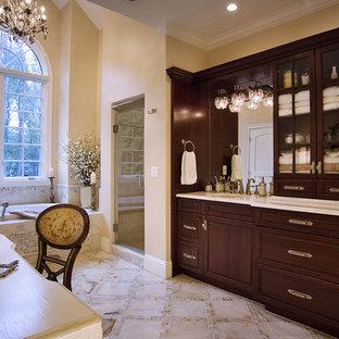 Imagen de cuarto de baño principal, tradicional, de tamaño medio, con armarios estilo shaker, puertas de armario de madera en tonos medios, bañera japonesa, ducha empotrada, baldosas y/o azulejos multicolor, baldosas y/o azulejos en mosaico, paredes amarillas, suelo de mármol, lavabo integrado y encimera de mármol