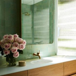 Inredning av ett modernt vit vitt badrum, med släta luckor, skåp i mellenmörkt trä, grön kakel, gröna väggar och ett integrerad handfat