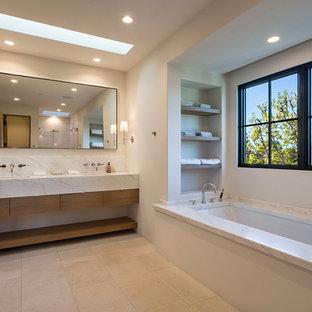 Ispirazione per una stanza da bagno padronale design con ante lisce, ante in legno scuro, vasca sottopiano, pareti bianche e pavimento beige