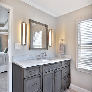 Inspiration for a large timeless master beige tile and porcelain tile porcelain tile and beige floor bathroom remodel in Atlanta with recessed-panel cabinets, gray cabinets, beige walls, an undermount sink, marble countertops and a hinged shower door