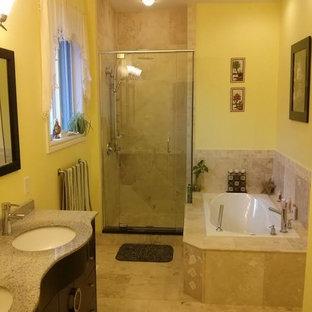 Idee per una stanza da bagno padronale tradizionale di medie dimensioni con consolle stile comò, ante in legno bruno, vasca da incasso, doccia alcova, piastrelle beige, piastrelle in travertino, pareti gialle, pavimento in travertino, lavabo sottopiano, top in granito, pavimento beige e porta doccia a battente