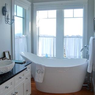 Imagen de cuarto de baño principal, marinero, pequeño, con puertas de armario blancas, bañera exenta, paredes grises, suelo de madera en tonos medios, lavabo sobreencimera, armarios con paneles empotrados, encimera de acrílico y suelo marrón