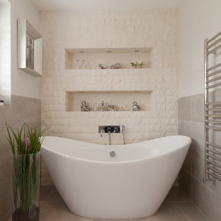 Design ideas for a classic bathroom in Surrey with a freestanding bath, white tiles, stone tiles and white walls.