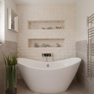 Idee per una stanza da bagno chic con vasca freestanding, piastrelle bianche, piastrelle in pietra e pareti bianche