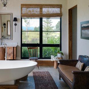 Foto de cuarto de baño principal, rural, grande, con armarios con paneles lisos, puertas de armario de madera oscura, bañera exenta, paredes blancas, lavabo bajoencimera, encimera de mármol y baldosas y/o azulejos de piedra