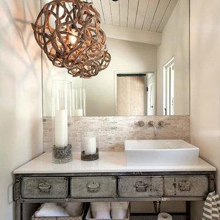 Ispirazione per una stanza da bagno costiera con lavabo a bacinella, ante con finitura invecchiata, pareti bianche, pavimento in legno massello medio e nessun'anta