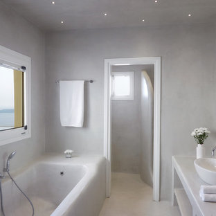 This is an example of a mediterranean ensuite bathroom in London with open cabinets, yellow cabinets, a built-in bath, white walls, white floors and white worktops.
