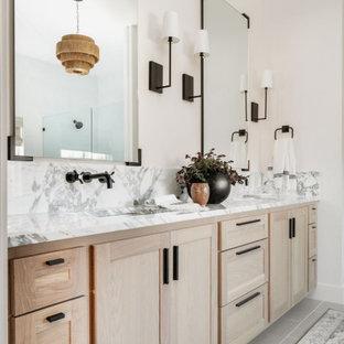 Bild på ett stort vintage vit vitt en-suite badrum, med skåp i shakerstil, skåp i ljust trä, ett fristående badkar, en dubbeldusch, en toalettstol med hel cisternkåpa, vit kakel, porslinskakel, vita väggar, klinkergolv i porslin, ett väggmonterat handfat, marmorbänkskiva, grått golv och dusch med gångjärnsdörr