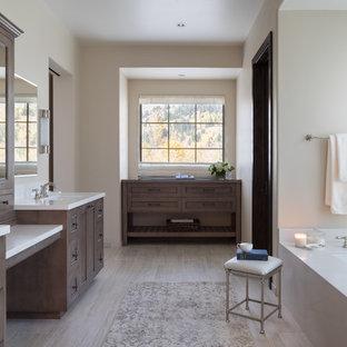 Imagen de cuarto de baño principal, rústico, con armarios con paneles empotrados, puertas de armario marrones, bañera encastrada sin remate, encimeras blancas, paredes blancas y suelo gris