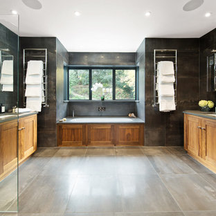 Inspiration for a traditional ensuite bathroom in London with shaker cabinets, medium wood cabinets, an alcove bath, black tiles, grey tiles, black walls, a submerged sink, grey floors and an open shower.