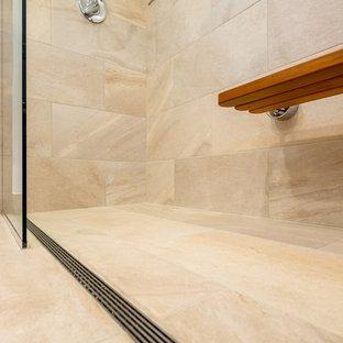 Klassisk inredning av ett en-suite badrum, med släta luckor, skåp i mellenmörkt trä, en kantlös dusch, beige kakel, vita väggar, klinkergolv i porslin, ett nedsänkt handfat och kaklad bänkskiva
